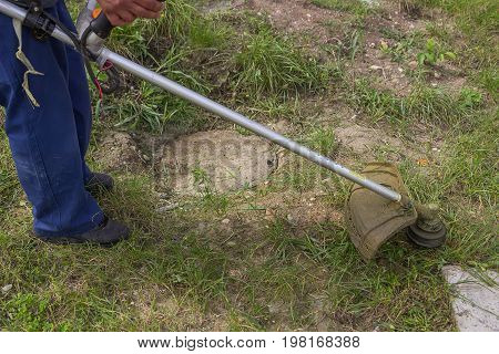 Worker Mowing The Grass With Gas String Trimmer