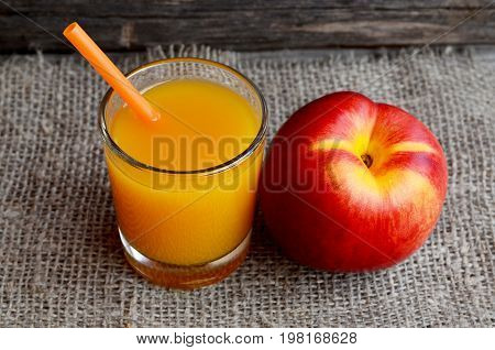 Fresh ripe organic nectarine and a glass of juice on burlap cloth.Nectarine juice.Peach juice.Diet,healthy food,raw food concept.Selective focus.