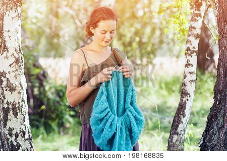 A dark-haired slender woman in a romantic light top and a wide skirt knits a blue and blue mohair thread sweater standing in a birch forest on a sunny summer day knitting with knitting needles