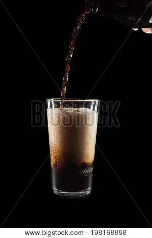 International Beer Day. Stout ale being poured in to a pint glass. Against black background with copy space. Stream of dark frothy stout beer flowing from a bottle in to a glass.
