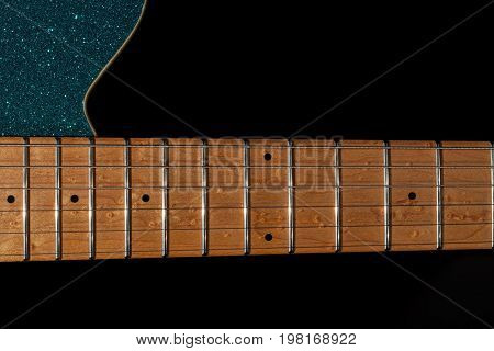 Guitar neck at the 12th fret. Maple fretboard portion on blue glitter electric rock guitar. Instrument neck shown against plain black background with copy space.