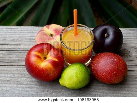 Fresh ripe fruits and a glass of juice in tropical garden.Multi fruit juice.Juice mix fruit on wooden table.Healthy drink or diet concept.Selective focus.
