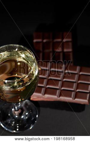 Wine and chocolate. Glass of white wine with a bar of chocolate in the background. Luxury comfort food for an evening of rest and relaxation.