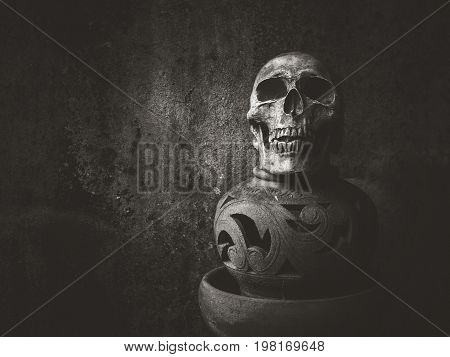 Still life with human skull and art pottery on abstract background