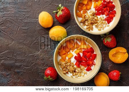 Natural yoghurt with pieces of apricots, strawberries, granola and pine nuts in two bowls on dark broun background. Top view with place for text