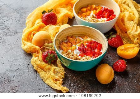 Natural yoghurt with pieces of apricots, strawberries, granola and pine nuts in two bowls on dark broun background