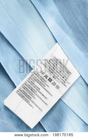 Washing instructions clothes label on blue satin as a background