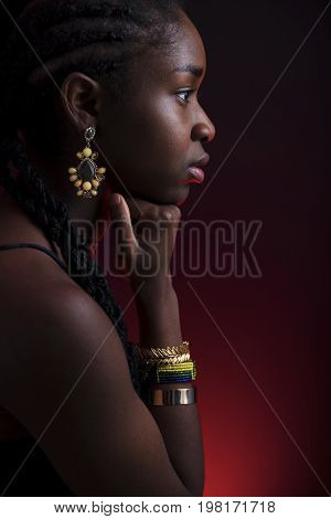 Colorful and creative side view portrait of african woman with dark skin and braided hair on red lit background.