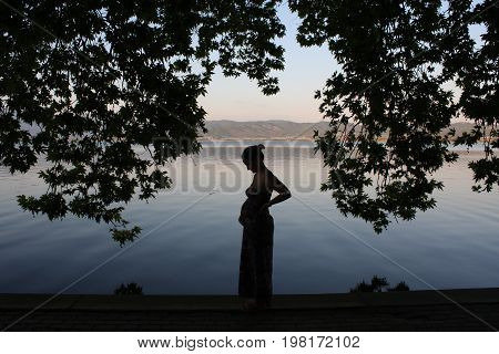 Silhouette of pregnant woman relaxing by the lake.