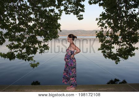 Young and pregnant woman relaxing next to the lake.