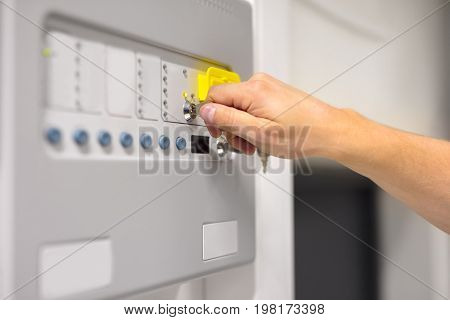 Closeup of IT engineer using key to open fire panel in datacenter
