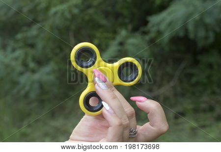 Spinner in a girl's hand against a background of bushes