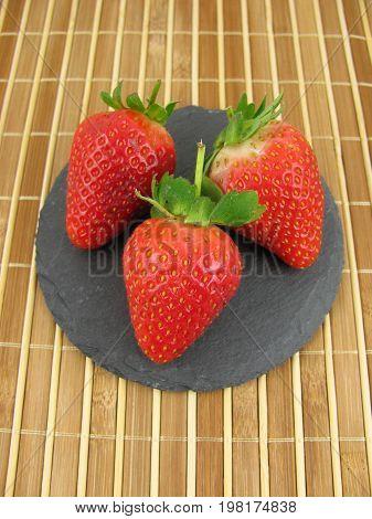 Fresh tasty strawberries on a slate plate