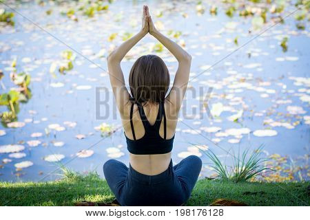 Woman Practicing Yoga On The Lawn Near The Pool.