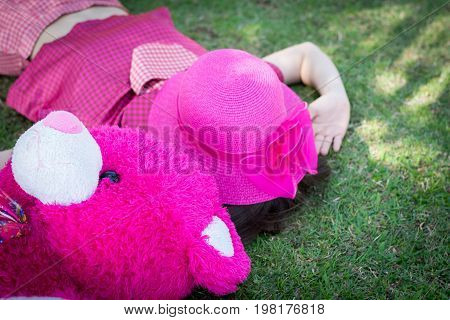 Happy Woman Sleep With Doll On The Grass Near The River.