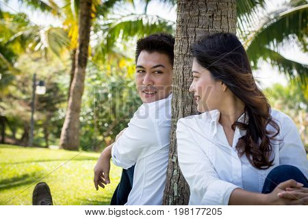 Young Happy Lovely Couple Sitting In The Green Park. Man Look At Young Woman Under The Coconut Tree.