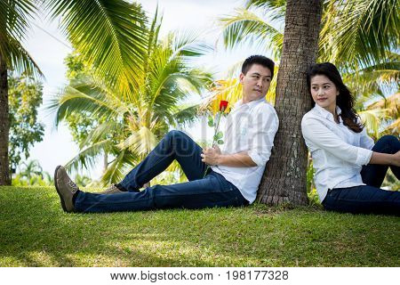 Young Happy Lovely Couple Sitting In The Green Park. Under The Coconut Tree. Man Giving Red Roses To