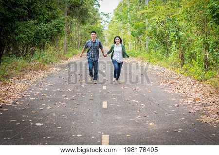 Couples Holding Hands Running Down The Street.