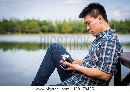 Hipster Man Sitting On The Lake Pier With Holding Vintage Camera, Relaxed Atmosphere, Summer.