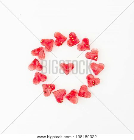 Water melon cut into heart shape. Flat lay composition on white background. Top view