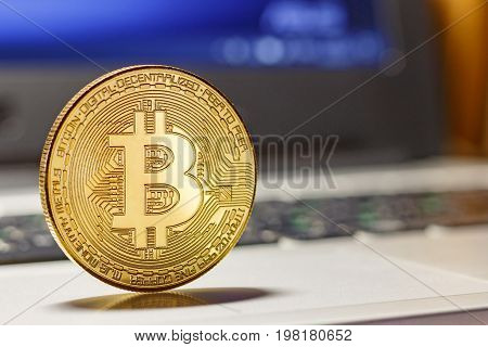 Golden Bitcoin On The Laptop Touchpad Closeup. Cryptocurrency Virtual Money