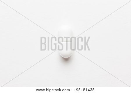 close-up of a pill. a pill on white background. white pill not isolated. white pill central composition