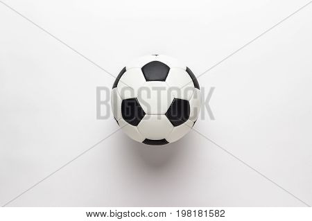 black and white leather soccer ball. top view of soccer ball on the white backgound. soccer ball not isolated on white table. soccer ball central composition