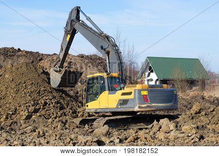 LENINGRAD REGION, RUSSIA - MARCH 09 2017: Yellow crawler excavator on work