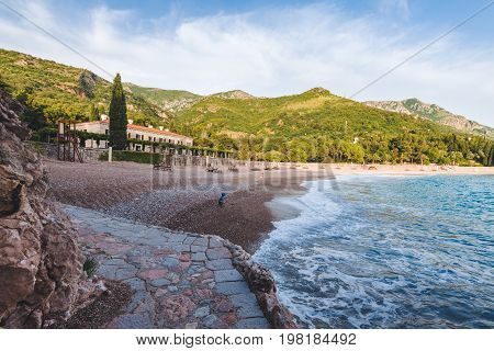 Wide angle view of Milocer Hotel and Royal beach near Sveti Stefan, Montenegro. Evening landscape with Adriatic sea, Milocer mansion and private King's and Queen's beach with mountains.