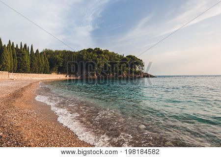 Wide angle view of Milocer Park and Royal beach near Sveti Stefan, Montenegro. Evening landscape with Adriatic sea, evening tide and private King's and Queen's beach with mountains.