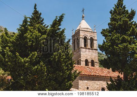 Rezevici abbey is situated between Budva and Petrovac, Montenegro.Stone belfry and facade of The Serbian Orthodox Rezevici Monastery located in Katun Rezevici village near Perazica Do.