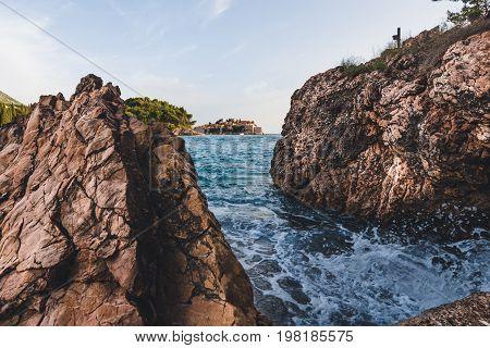 Sveti Stefan island and waves splashing on rocks near Budva, Montenegro on Adriatic coast. Evening view of Adriatic sea, St. Stefan luxury fortificated village and cliffs.