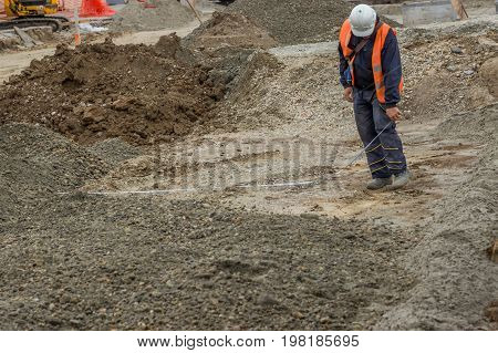 Construction Worker Measures The Width Of A New Road Lane