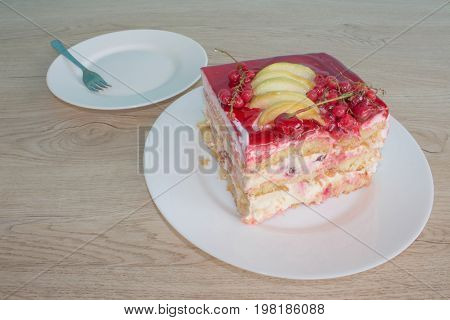 Fruit Cake with fresh red currant on the plate closeup. Close up cake with red currant