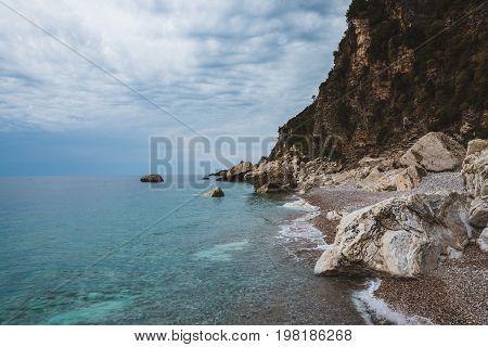 Wild scene with sea surf, cloudy sky, stones and rocks. Pebble beach and shoreline in Perazica Do near Rezevichi, Montenegro. Montenegrin coast and Adriatic sea by cloudy day. Montenegro landscape.