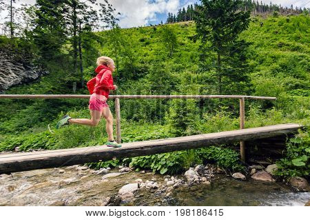 Girl trail running in mountains on summer sunny day. Female trail runner crossing bridge on a mountain river. Sport and fitness concept outdoors in nature.