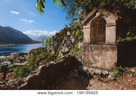 Small stone shrine on the path to Kotor's castle along the fortress wall. Kotor Bay, Old Town and mountain view on the background.
