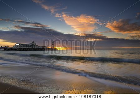 The sun rises over the sea at Bournemouth illuminating the cloads and the sea