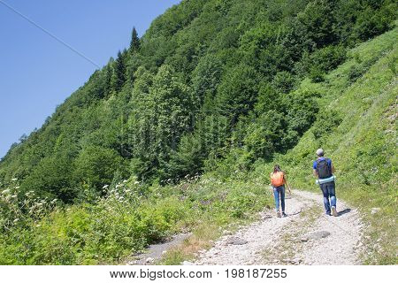 Active and healthy lifestyle on summer vacation and weekend tour. Group of tourists hitching a ride. Travel adventure and hiking activity. Two young Tourists With Backpacks travel