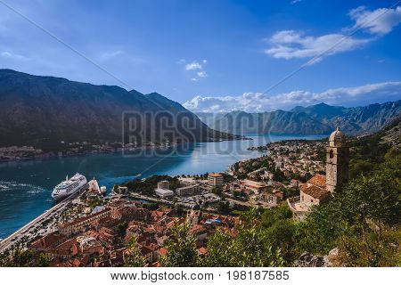 Kotor Bay and Old Town view from above Kotor's castle of San Giovanni. Stone staircase, traditional house roofs, cathedral dome and Boka Kotorska wide angle view.