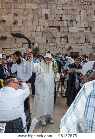 JERUSALEM, ISRAEL - OCTOBER 12, 2014: . Elderly religious Jew with a Shofar. Morning autumn Sukkot. The area in front of Western Wall of  Temple filled with people