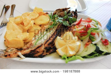 Dish with grilled seabass baked potato chips fresh salad, celery and lemon on white plate isolated at restaurant table. Cooked whole fish and vegetables tasty simple healthy food product dinner option