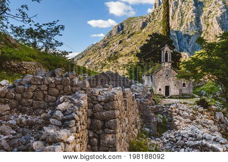 Ancient Serbian church, city ruins and mountain valley landscape near Kotor castle, Montenegro. Old mountain church and monastery in Kotor Bay area on hike path to Lovchen mountain. Saint Ivan chapel.