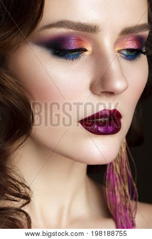 Close up portrait of beautiful young woman with professional makeup, perfect skin, wavy hair, long earrings. Trendy colorful smoky eyes.