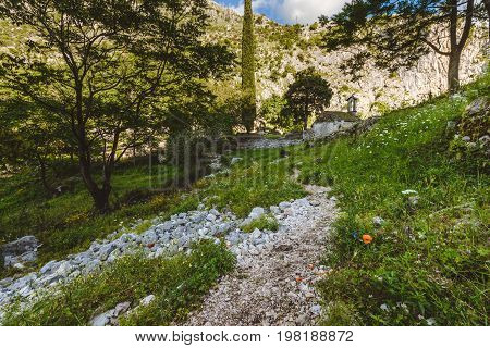 Ancient Serbian church ruins and mountain valley landscape near Kotor castle in Montenegro. Old mountain church and monastery in Kotor Bay region near hike path to Lovchen mountain. Saint Ivan chapel.