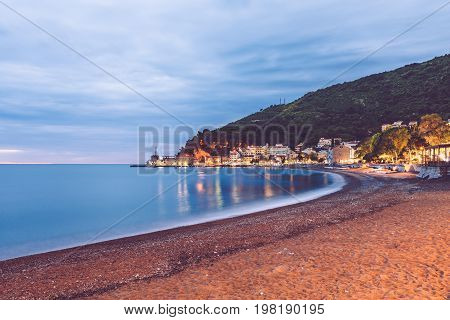 Petrovac village night scene with montenegrin houses, Castello fortress, seaview and evening lights reflected in the water of Adriatic sea. Touristic town Petrovac harbor panorama, Montenegro.