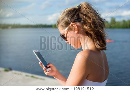 Young cute teen girl reading sms on her smartphone view from behind. Against the background of the river in the city.