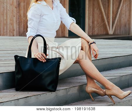 Part of body. Girl sitting on the stairs with a big black super fashionable handbag in a dress and Wide Fit Pointed Heels on a warm summer evening. Fashion. Bag.