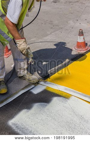 Worker Hand Holding Industrial Airless Spray Gun And Paint Stripes