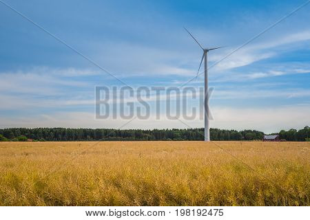 Windmill in landscape with yellow wheat field, forest and red house in the background. Dramatic spectacular blue sky with clouds, yellow and green colors. Clean, green eco energy concept.